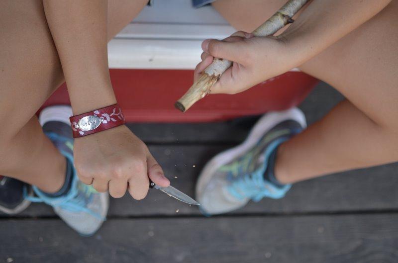 Ein Kind schnitzt mit einem Taschenmesser.