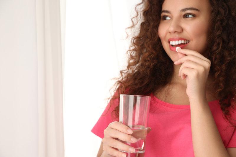Einnahme einer Tablette mit Wasser