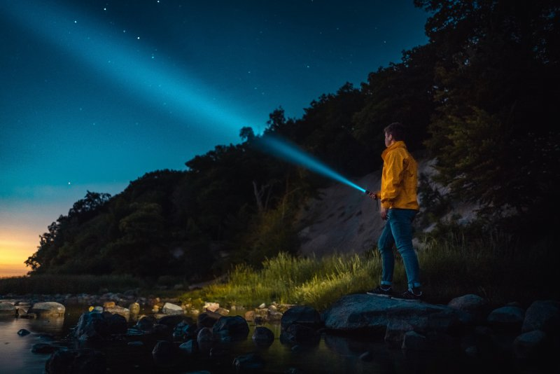 Mann leuchtet mit Taschenlampe nachts