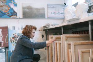 Eine Frau durchsucht mehrere Malerleinwände.