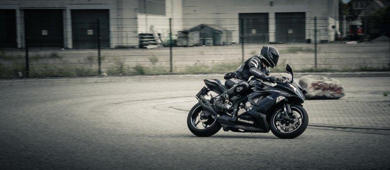 Person auf einem Motorrad, fahrend auf einer Rennstrecke in einem sportliche Kombi