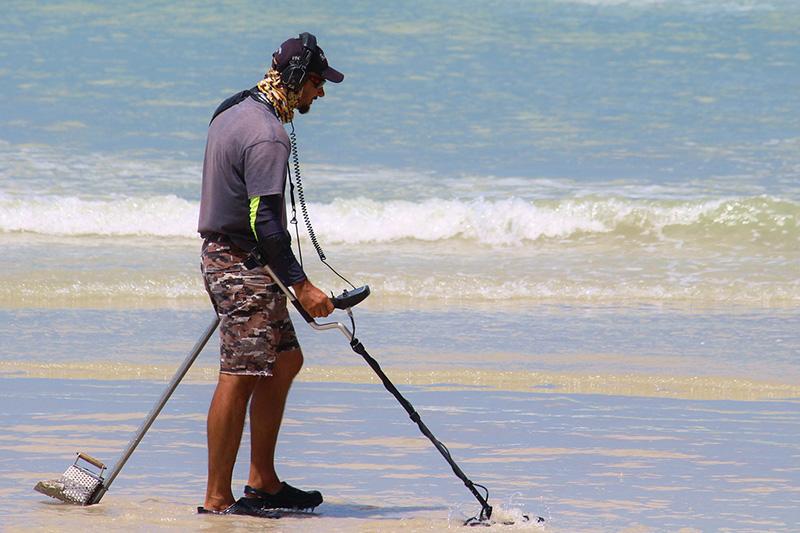 Mann mit einem Metalldetektor am Strand