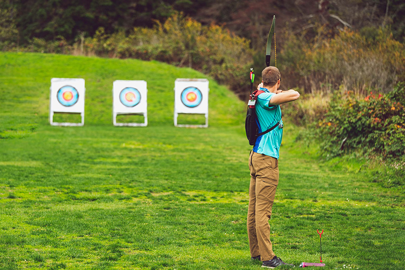 Mann zielt mit Bogen auf eine Zielscheibe