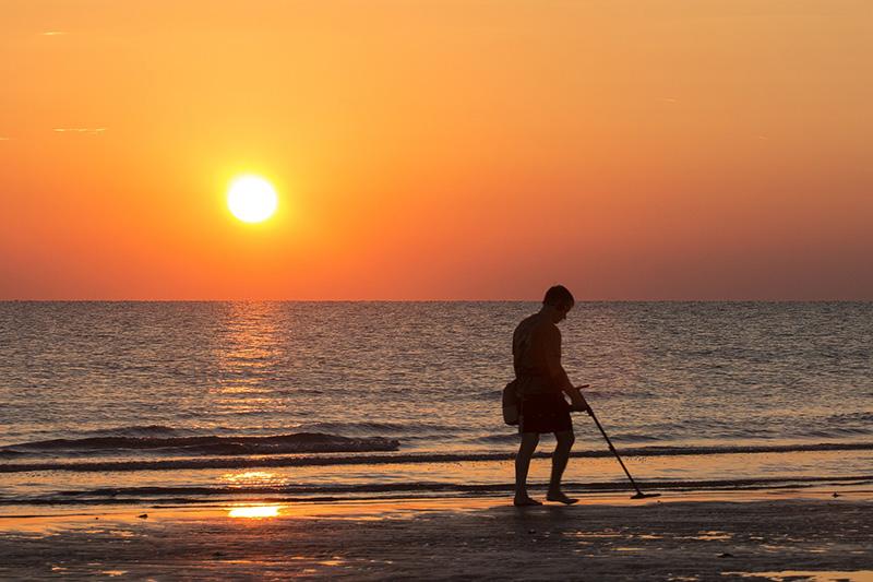 Mann mit Metalldetektor am Strand im Sonnenuntergang