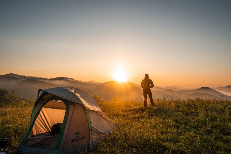 Bild zeigt Wanderer mit seinem Mini-Zelt auf Trekking-, Wander- oder Campingtour in der Natur bei Sonnenaufgang.