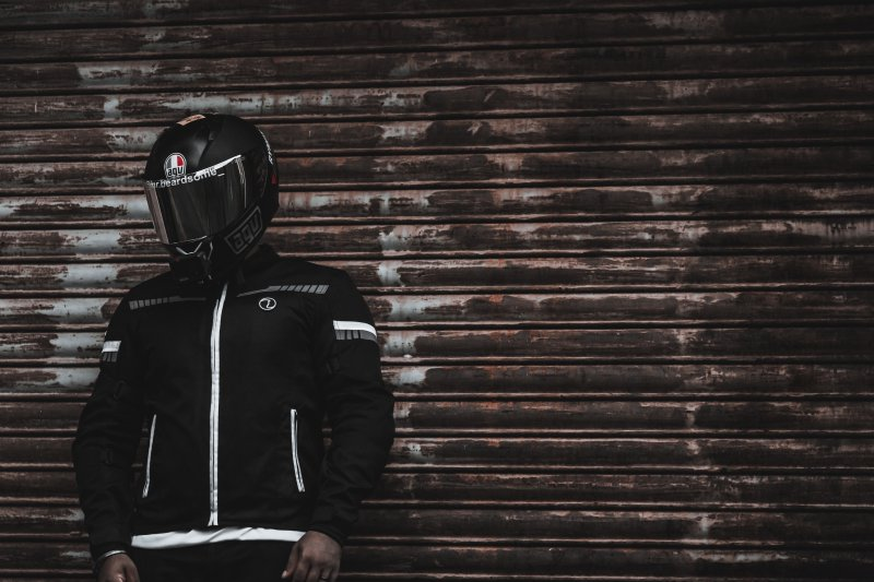 Person in Motorradjacke aus Textil und Helm vor einer Holzwand