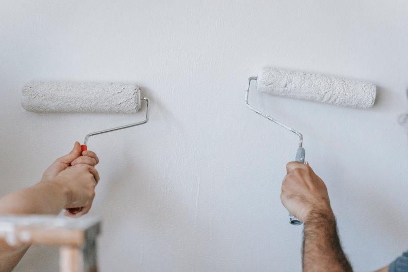 Zwei Hände streichen eine Wand
