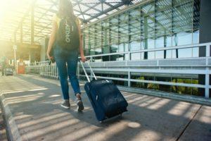 Reisende zieht ihre Reisetasche mit Rollen