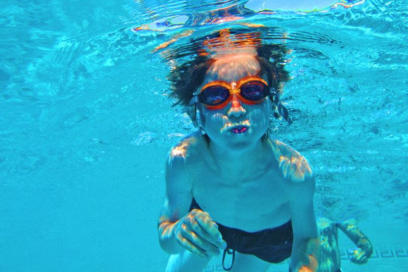 Ein Kind taucht in einem Swimmingpool. Es trägt eine Schwimmbrille.