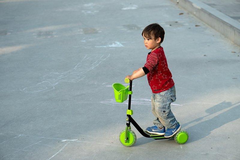 kleines Kind auf einem Tretroller