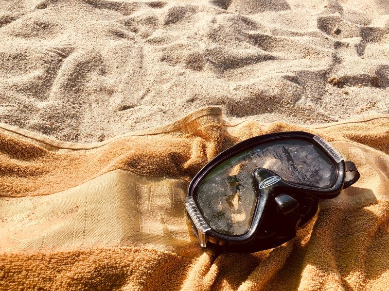 Eine Taucherbrille mit beschlagenen Gläsern liegt auf einem Handtuch am Strand.