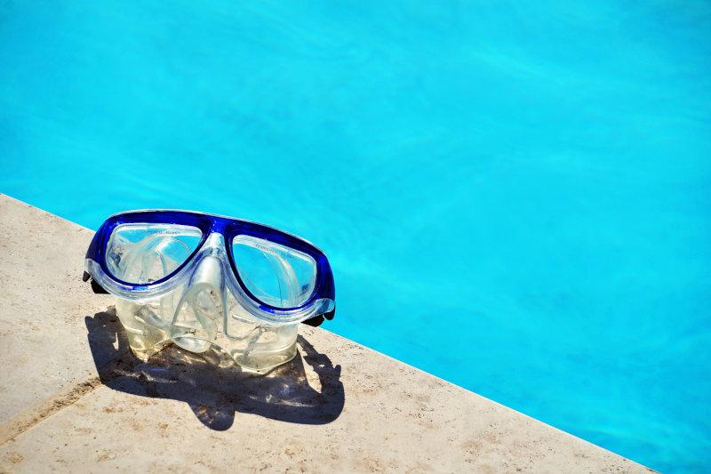 Eine Taucherbrille liegt auf einem Schwimmbeckenrand. Im Hintergrund sieht man blaues Wasser.