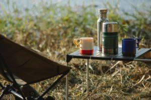 Thermoskannen auf einem Tisch beim Campen am See