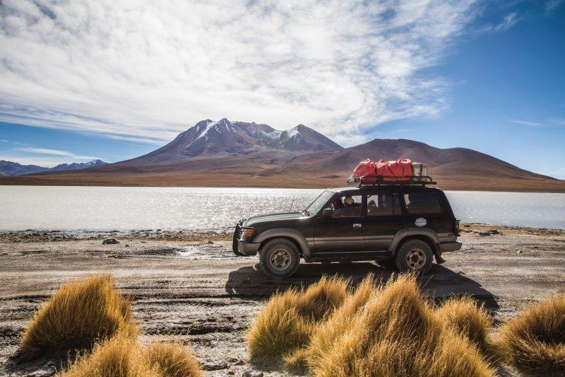 Ein Auto steht vor einer schönen Landschaft und hat Gepäck auf dem Dach.