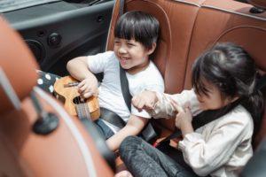 Kinder sitzen hinten in einem Auto und haben Spaß.