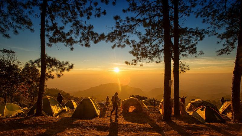 Trekkingzelte und Menschen bei Sonnenuntergang