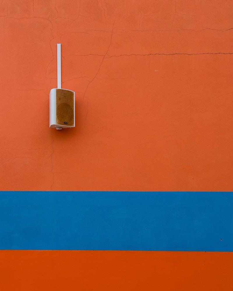 Ein weißer Wandlautsprecher auf einer orangen Wand mit einem blauen Streifen - das ist Design pur!
