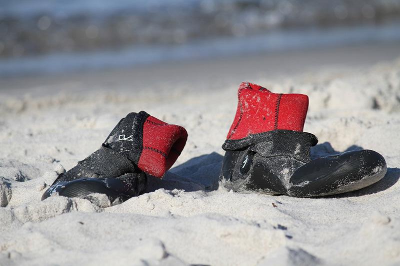 Wasserschuhe stehen im Sand