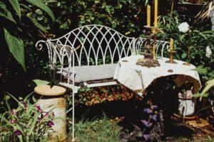 Weiße Sitzbank aus Metall im Garten