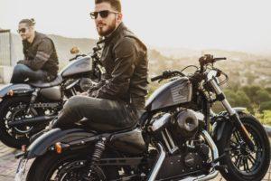 Zwei Männer, sitzend auf Motorrädern in Motorradjacken aus Leder
