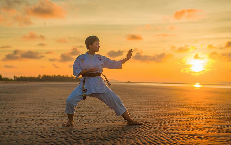 Karateka macht eine Kata im Sonnenuntergnag