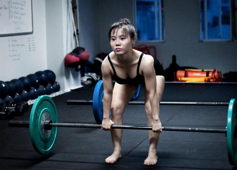 Frau beim Training mit der Langhantel (Kreuzheben)