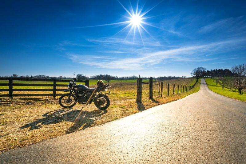 Ein schwarzes Motorrad am Wegesrand in strahlendem Sonnenschein