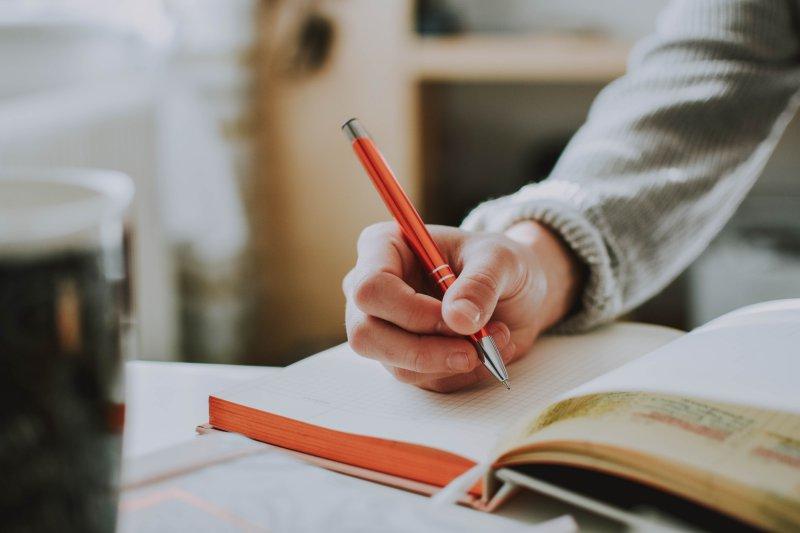Person schreibt in ein Notizbuch