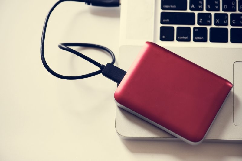 Ein rotes externes DVD Laufwerk auf einem Notebook