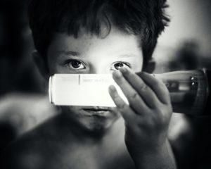 Ein Kind hält sich eine Kinder-Taschenlampe vor sein Gesicht