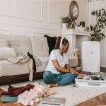 Frau packt auf Boden Koffer und hört Musik