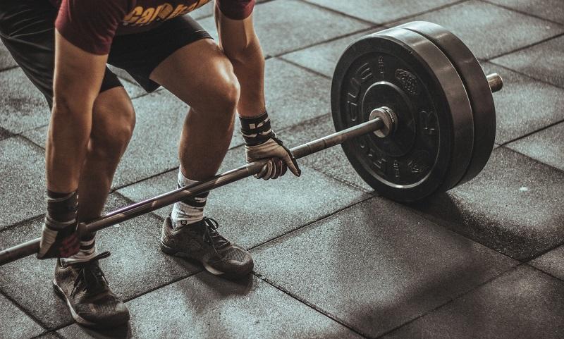 Mann greift an Langhantel mit schweren Gewichten