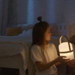 Kind hält eine Leselampe vor ihr Bett