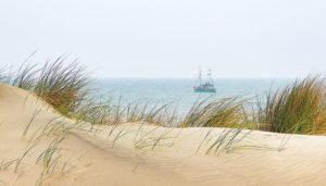 Die Dünen der Nordsee vor dem Meer selbst - mit einem vorbei tuckerndem Schiff ein wahrgewordener Traum.
