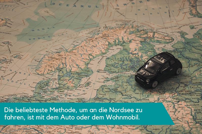 Ein kleines Spielzeugauto, platziert auf einer Karte, die den nördlichen Teil Deutschlands und Finnland zeigt. Die Beschriftung lautet: Die beliebteste Methode, um an die Nordsee zu fahren, ist mit dem Auto oder dem Wohnmobil.
