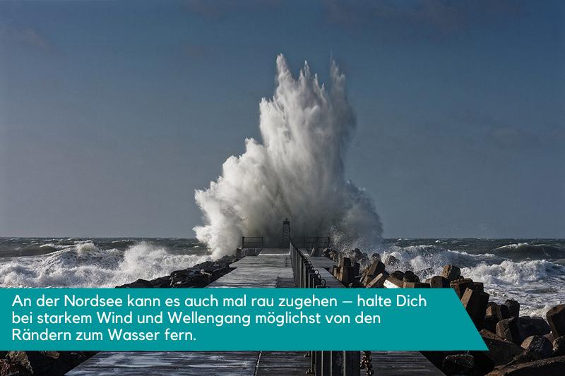 Eine massive Welle, die an der Nordsee auf einen Deich prallt - ein wahres Naturschauspiel. Die Beschriftung lautet: An der Nordsee kann es auch mal rau zugehen - halte Dich bei starkem Wind und Wellengang möglichst von den Rändern zum Wasser fern.
