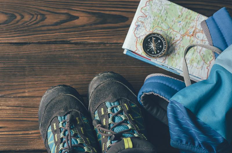 Foto von Wanderschuhe, Wanderrucksack, Kompass und Wanderkarte im Flatlay