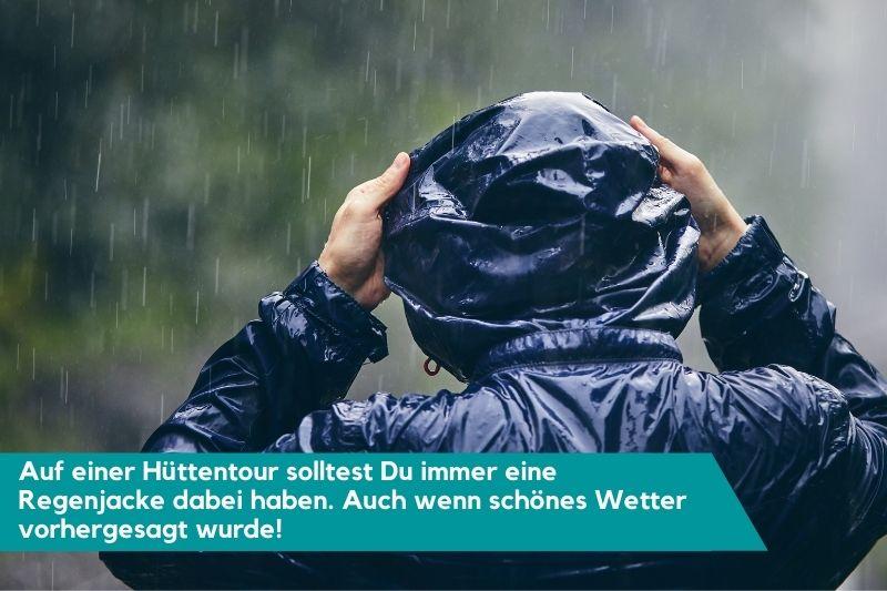 Person von hinten im Regen mit Regenjacke