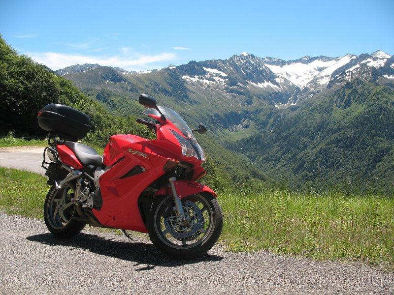Ein rotes Motorrad an der Straße mit Blick auf die Berge
