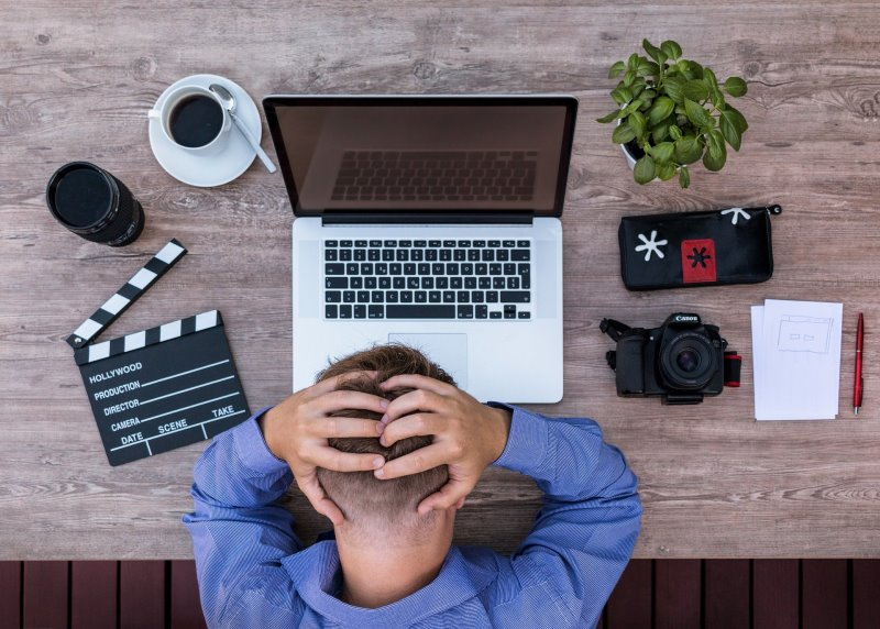 Mann sitzt vor einem PC und hat eine Schreibblockade