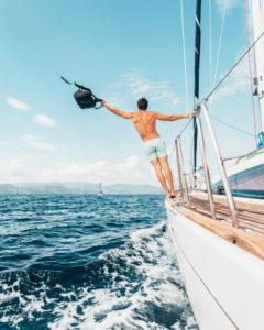 Der Mann genießt den Urlaub auf dem Segelboot