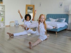 Zwei Kinder machen Spagat in einem Zimmer