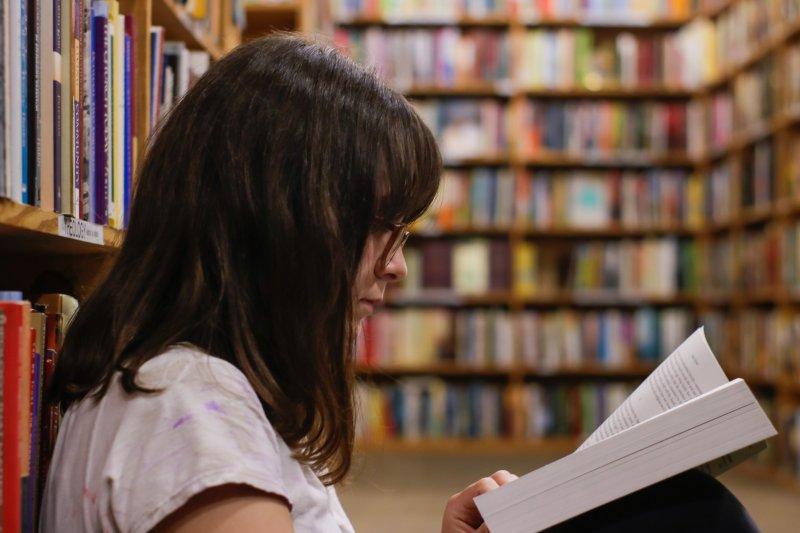 Frau liest ein Buch vor Bücherregalen