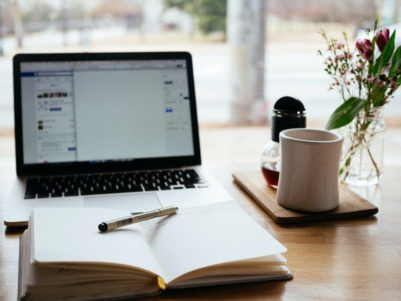 Laptop und Notizbuch auf einem Tisch