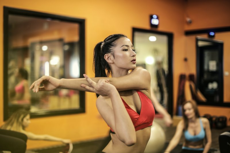 Sportliche Dame macht Dehnübungen mit Eigengewicht