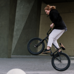 Eine Frau die ein BMX-Trick demonstriert.