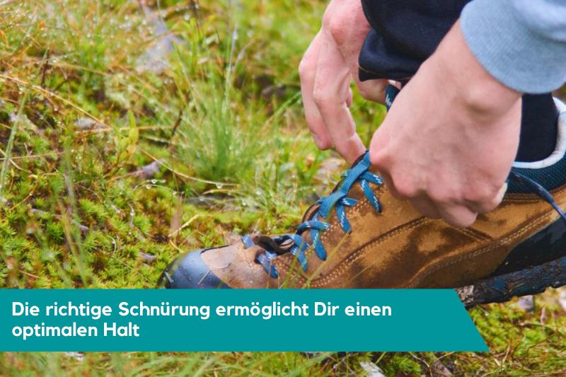 Braune Zustiegsschuhe mit blauen Schnürsenkel auf Wiese werden geschnürt.