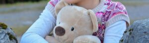 Kind hält Stofftier-Teddybär im Arm