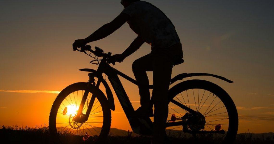 Mann auf E-Moutainbike Offroad im Sonnenuntergang