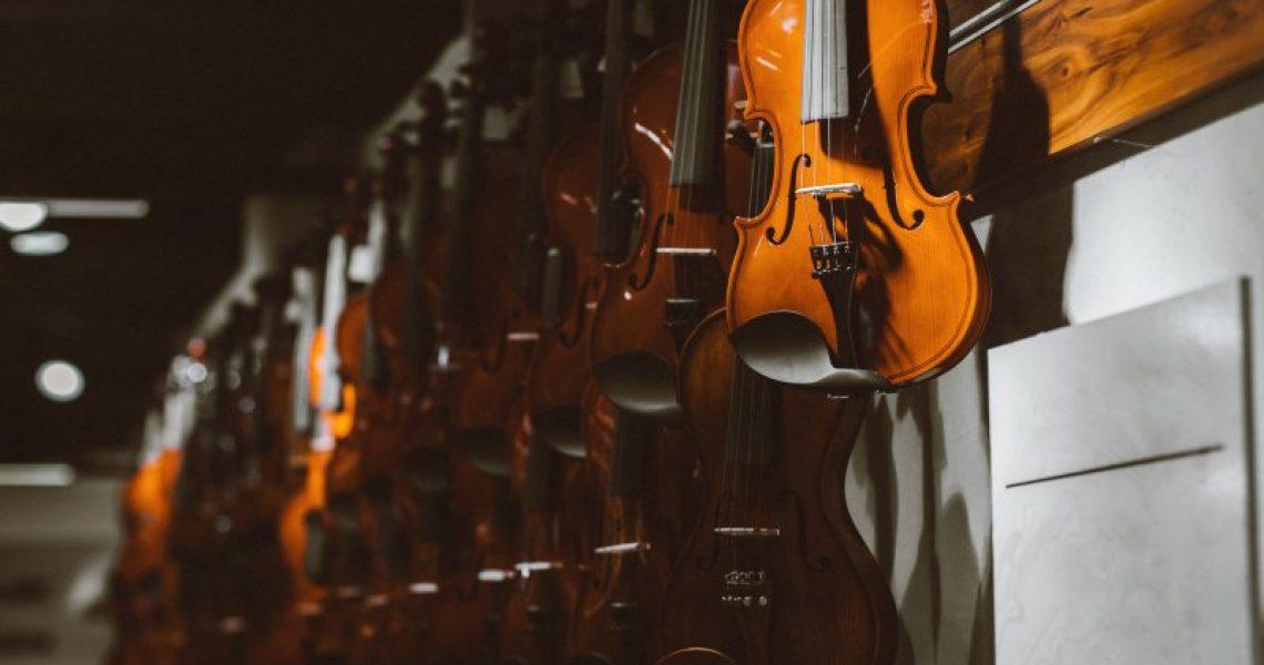 verschiedene Geigenmodelle hängen an der Wand